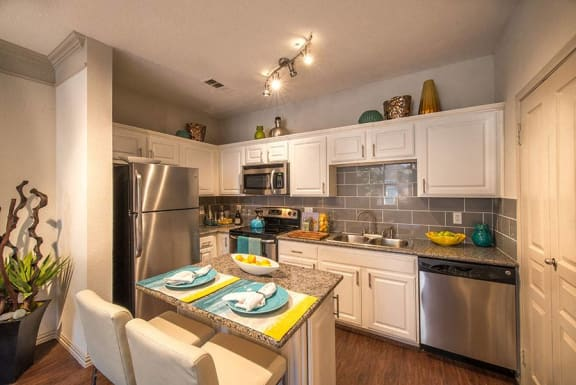 This is a photo of the kitchen area of the 826 square foot 1 bedroom  apartment at The Brownstones Townhome Apartments in Dallas, TX.