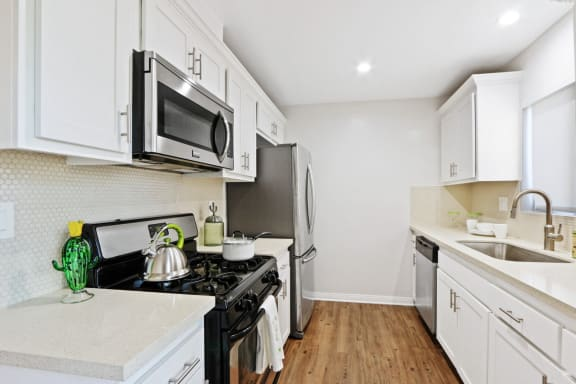 Renovated kitchen with stainless steel French door refrigerator, gas stove over microwave range hood, dishwasher, single kitchen sink, wood style floors, white cabinets, light quartz counter tops, tile backsplash