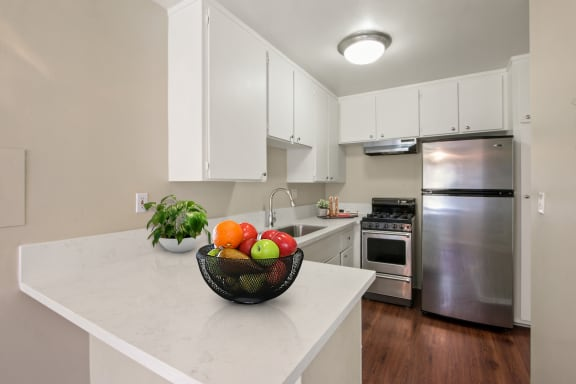 Kitchen Kitchen with stainless steel two-door refrigerator, gas stove over range hood, white cabinets, quartz counter tops