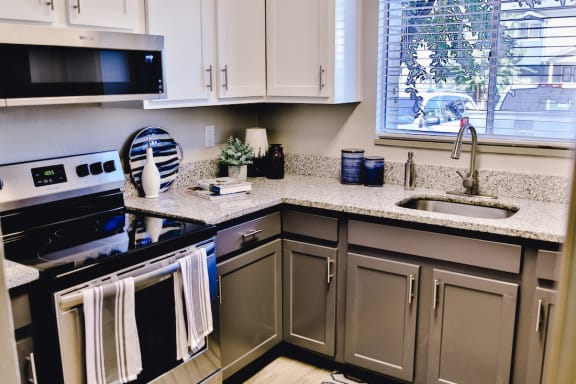 kitchen with stainless steel oven and flat cook top and granite countertops at The Jameson Apartments, Homewood, AL, 35209