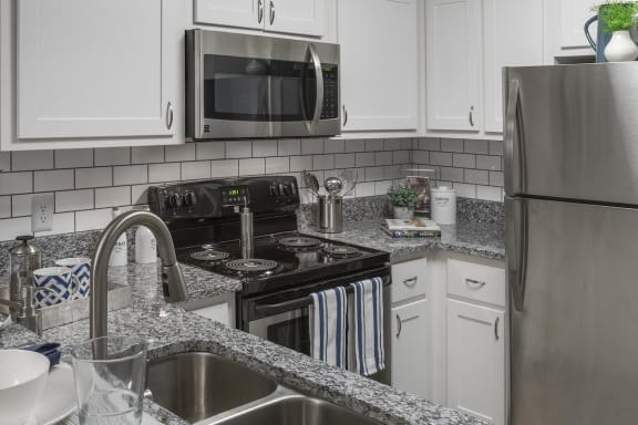 modern kitchen with subway tile, stainless steel appliances, granite countertops