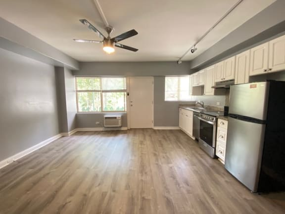 Hobron Apartments living area and kitchen area with appliances and cabinets