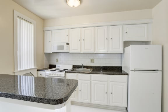 kitchen with white cabinetry, stone countertops and isolated countertop  at Tivoli Gardens Apartments in Washington, DC