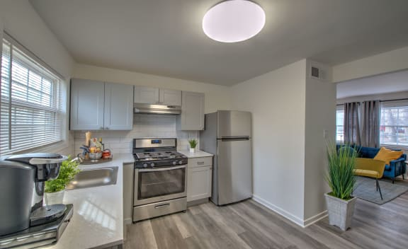 kitchen at Crestwood at Libbie apartments in Richmond, VA with stainless steel appliances, light cabinets, hardwood flooring and stone countertops