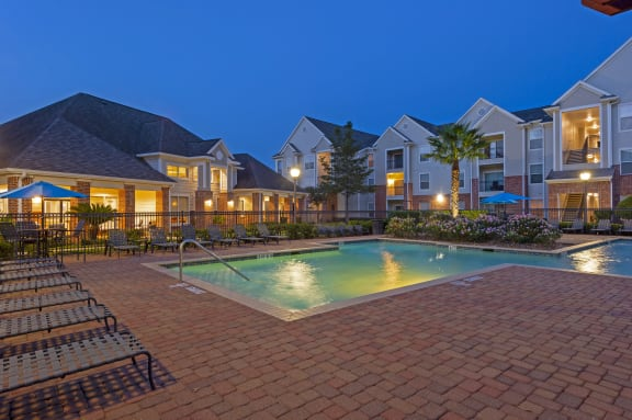 Pool view with side lounge chairs and clubhouse in the background at dusk