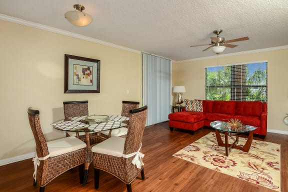Livingroom / Dining room combo with hard wood style flooring, light fixture over table and ceiling fan in  the Livingroom.