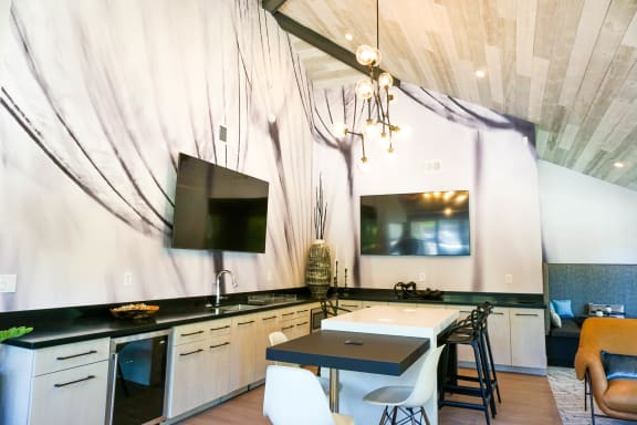 Sorelle Apartments resident lounge with 2 big screen TVs, a kitchen with black countertops and white cabinets, a kitchen island with black barstools, and vaulted ceilings