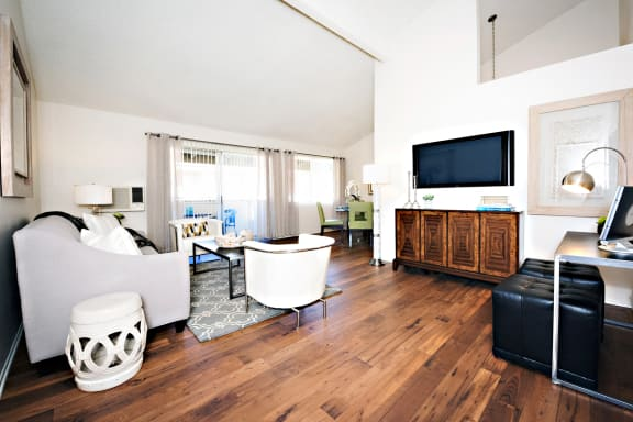 Oakview's upstairs apartment living room area has vaulted ceilings, with either wood vinyl flooring or carpet. The walls are while and has a patio sliding door leading to a patio..