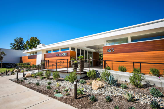 The Biltmore Apartments modern exterior lighting and beautiful tan color wood style siding. In addition, there is a pathway with a few steps to the breezeway entrance leading to the leasing office.
