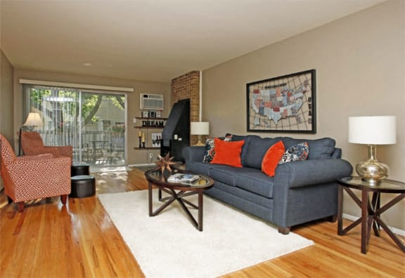 Living room with oak flooring, furniture, and balcony