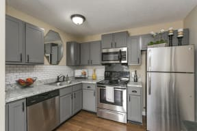 The Slate at Ninety-Six Modern Kitchen with Stainless Steel Appliances, Wood-Style Flooring, and Ample Cabinet Storage
