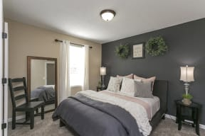 The Slate at Ninety-Six Master Bedroom with Plush Carpet Flooring, Large Window, and Two-Tone Colored Walls