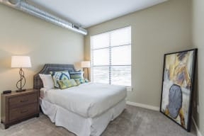 Gale Lofts Master Bedroom with Large Window and Carpet Flooring