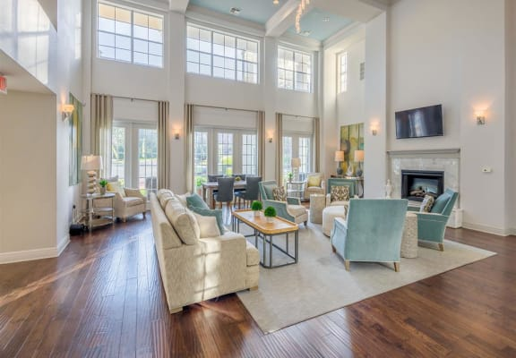 Resident clubhouse with TV, fireplace, seating areas and extra high ceiling at Evergreen at Mahan