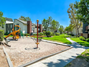 Ontario Apartments for Rent - Playground with Playground Equipment, Sand, Bench Seating, Surrounded by Lush Landscaping and Avante Apartment Buildings