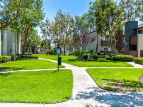 Apartments for Rent in Ontario - Walkway through Avante Apartment Buildings Surrounded by Lush Landscaping