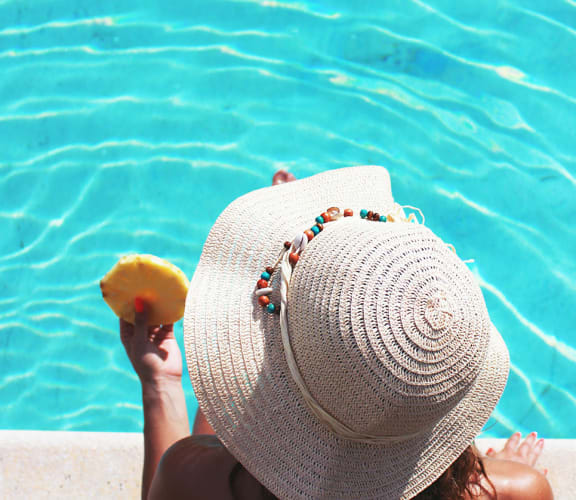 person dipping toes in pool with summer hat at The Sands Apartments in Mesa, AZ 85213