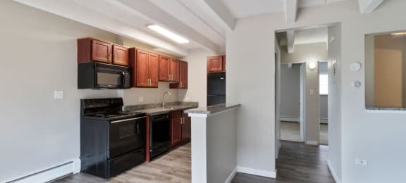 Spacious kitchen space featuring hardwood floors and all-black appliances