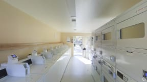 Laundry room view from back toward door with all machines in view