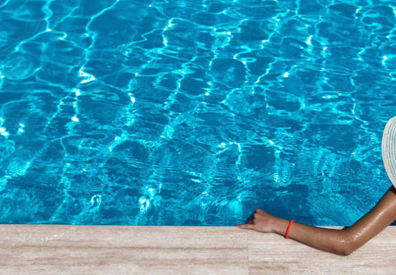 Back of woman with floppy hat in pool