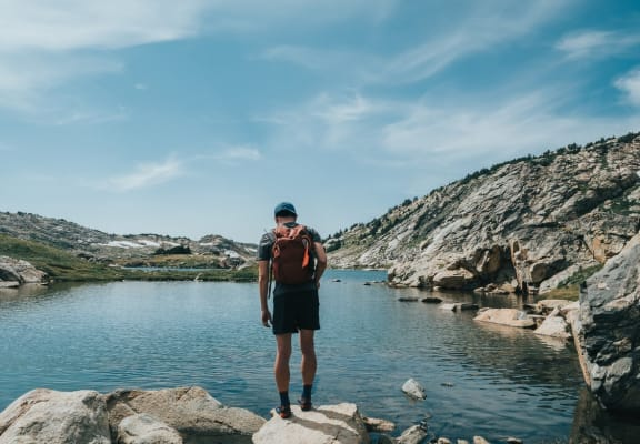 Man Standing By Rocky Shore of Lake