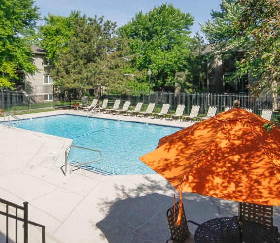 pool deck with cheery orange pool lounges at Crossroads Apartments in West Valley UT, 84119