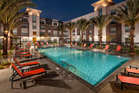 Pomona CA Apartments - Sparkling Resort Style Pool at Dusk Featuring Various Lounge Areas