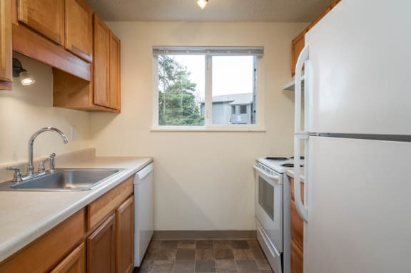 Birch Creek | Kitchen with Ample Wood Cabinetry and White Appliances