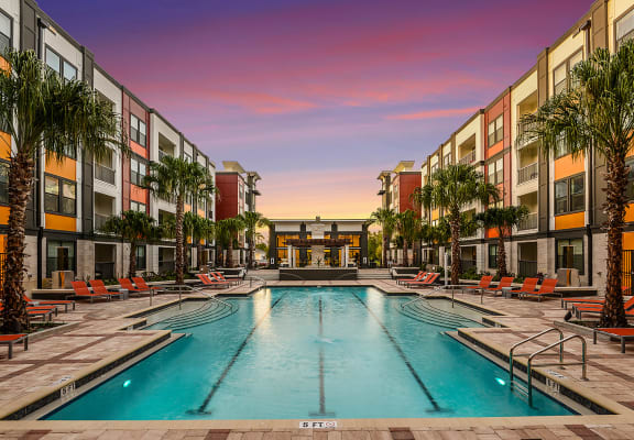 Resort-style swimming pool with large sundeck and lounge chairs at EOS Orlando