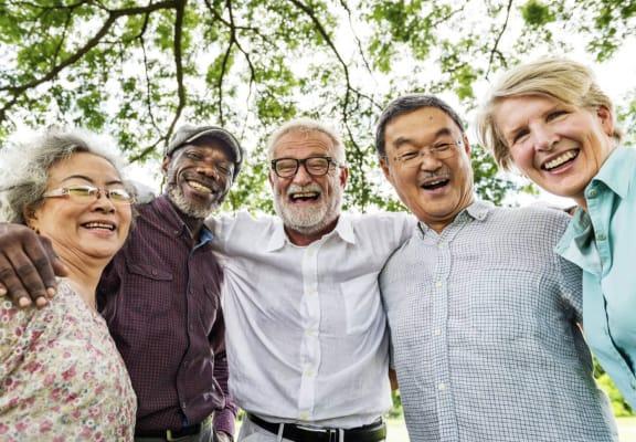 Four racially diverse, senior individuals huddled around smiling.
