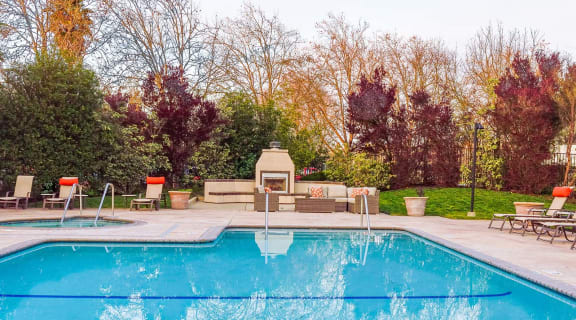 Pool with lounge chairs by fireplace l Vineyard Gardens