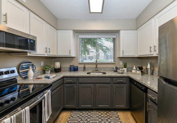 Upgraded kitchen with stainless steel appliances, granite countertops, dark cabinets below and white upper cabinets