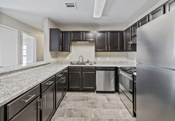 Newly renovated kitchen with stainless steel appliance, granite-style countertops, dark wood cabinetry, and new flooring