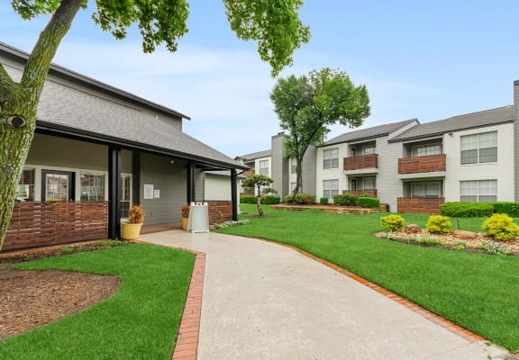 Clubhouse and leasing office back entrance showcasing well-kept landscaping and walking paths at Cobblestone Apartments.