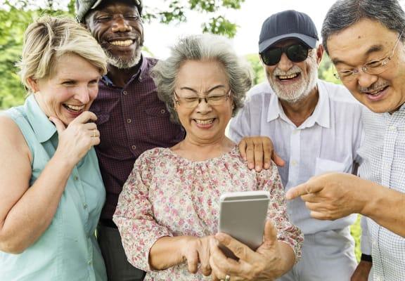 Senior Friends Looking at Phone | Serenity Villas Senior Apartments in Pomona, CA