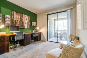 Office area with sliding glass doors to balcony
