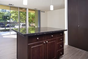 Kitchen island and living area with sliding glass doors to patio