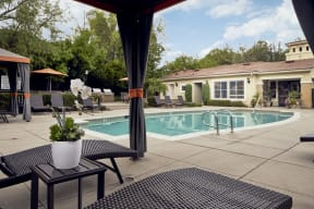 Outdoor pool area with cabanas
