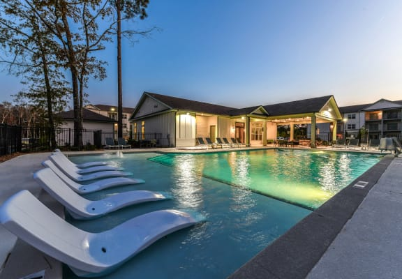 Resort-style swimming pool with in-water lounge chairs at Exchange at Windsor Hill
