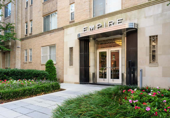 building exterior with grass on each side of walkway at Empire Apartments in Washington, DC