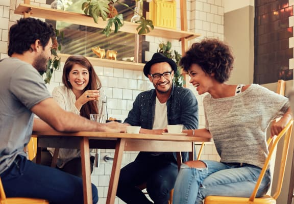 Four people sitting around a table chatting