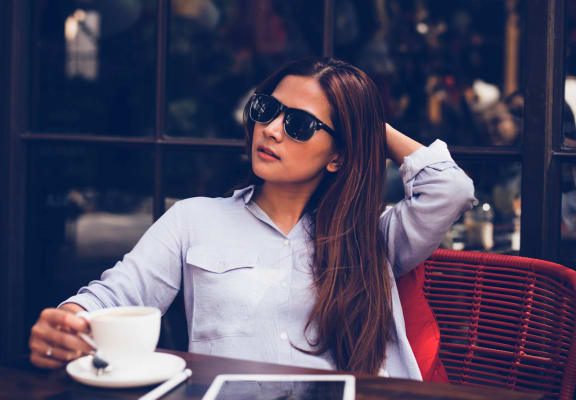 Woman in Sunglasses Sitting at Table at Cafe Patio