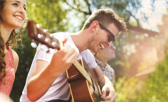 Lifestyle Image: A man playing a guitar laughing as he hangs out with his friends in an outdoor setting