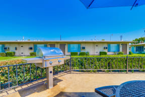 Apartments in Colton, CA - Enclosed Picnic Area Featuring Grill and Covered Tables with Bench Seating, Surrounded by Lush Landscaping and Las Brisas Apartment Buildings