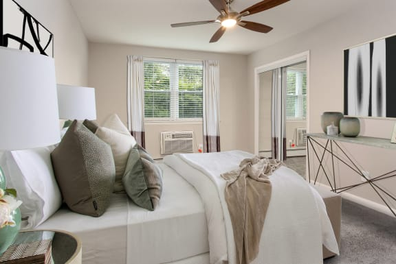 Furnished model of Master Bedroom with ceiling fan, mirror closet doors, and air conditioner installed in the wall under two windows.