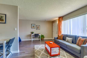 Colton Apartments for Rent - Las Brisas Living Room with Stylish Decor, Beige and Grey Walls, Plank Flooring, Large Window, and Popcorn Ceiling