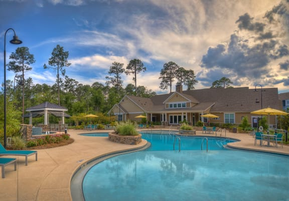 Exterior view of resort-style swimming pool with view of clubhouse at Lullwater at Blair Stone apartments for rent