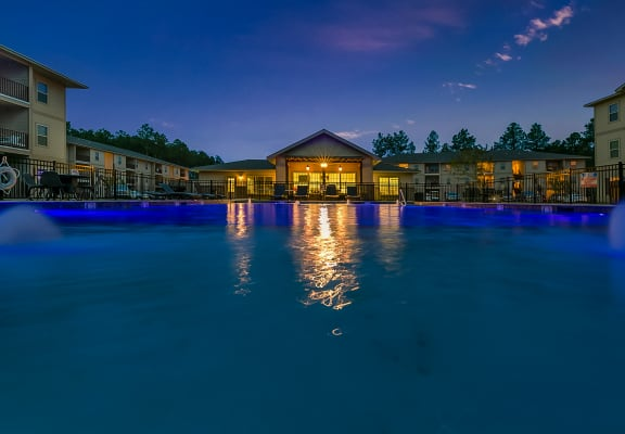 Looking across the swimming pool at night with the clubhouse patio lights at Reagan Crossing