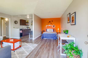 Las Brisas Apartments in Colton - Bedroom with Stylish Decor, Plank Flooring, Beige and Orange Walls, Small Shelf, and Popcorn Ceiling