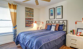 Bedroom with drapery, white nightstand, bed with blue bedding, ceiling fan, wall art and wood like style flooring.